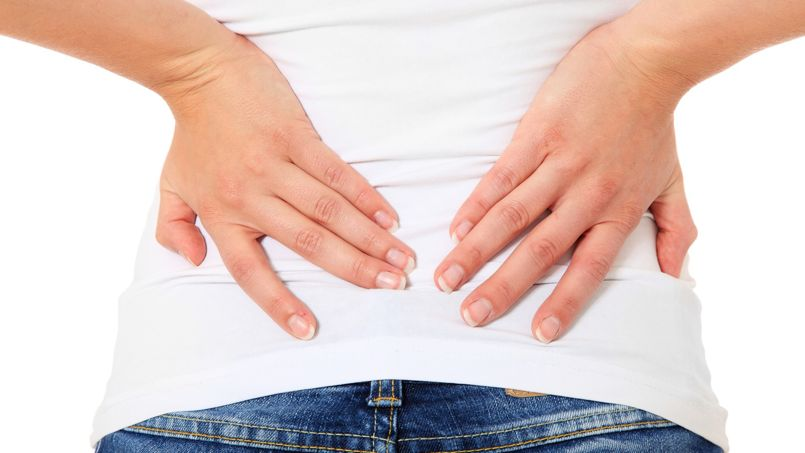Weibliche Person klagt über Rückenschmerzen